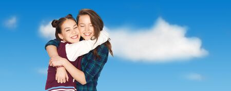 parejas felices: people, friends, teens and friendship concept - happy smiling pretty teenage girls hugging over blue sky and clouds background