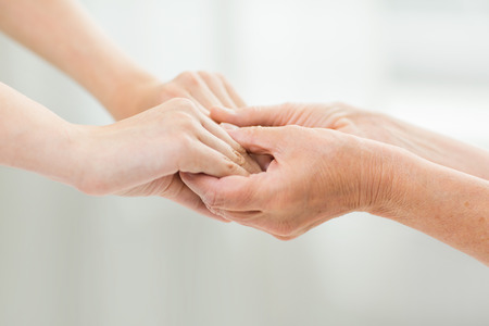 old hand: people, age, family, care and support concept - close up of senior woman and young woman holding hands