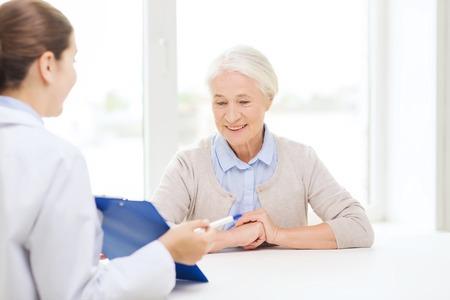 geneeskunde, de leeftijd, de gezondheidszorg en de mensen concept - arts met klembord en senior vrouw vergadering in het ziekenhuis Stockfoto