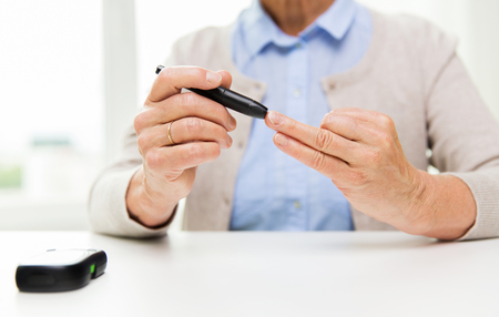 health woman: medicine, age, diabetes, health care and people concept - close up of senior woman with glucometer checking blood sugar level at home