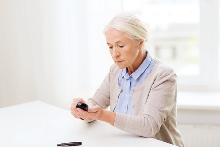 glucometer: medicine, age, diabetes, health care and people concept - senior woman with glucometer checking blood sugar level at home
