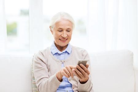 Technologie, Kommunikation Alter und Personen-Konzept - Glückliche ältere Frau mit Smartphone SMS-Nachricht zu Hause