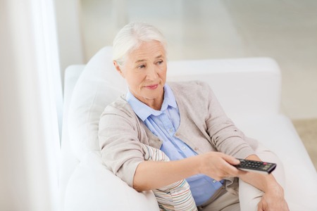 people watching: technology, television, age and people concept - senior woman watching tv and changing channel with remote control at home