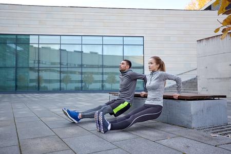 fitness, deporte, la formación, la gente y el concepto de estilo de vida - Pareja haciendo ejercicio tríceps por inmersión en banco al aire libre