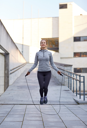 woman rope: fitness, sport, people, exercising and lifestyle concept - happy woman skipping with jump rope outdoors