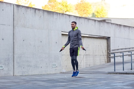 skipping rope: fitness, sport, people, exercising and lifestyle concept - man skipping with jump rope outdoors