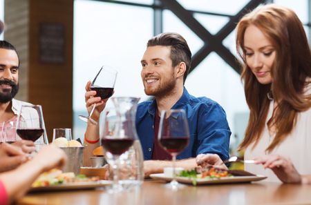 personas festejando: leisure, eating, food and drinks, people and holidays concept - smiling friends having dinner and drinking red wine at restaurant Foto de archivo