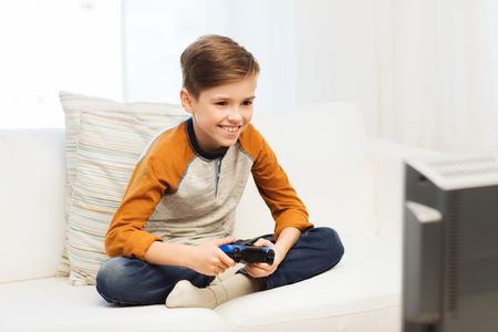 ocio, los niños, la tecnología y el concepto de la gente - muchacho sonriente con joystick jugando videojuegos en el hogar
