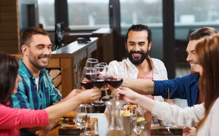 dinner party: leisure, celebration, food and drinks, people and holidays concept - smiling friends having dinner and drinking red wine at restaurant Stock Photo