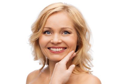 belleza, cuidado de la piel y de las personas concepto - sonriente mujer con los hombros descubiertos que tocan la cara