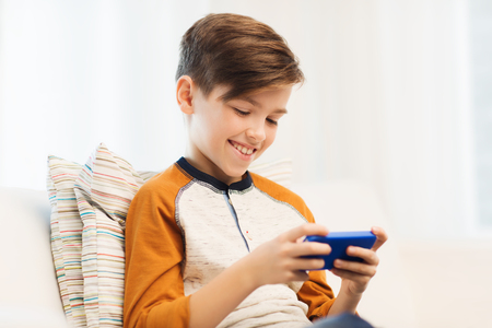 teenage male: leisure, children, technology, internet communication and people concept - smiling boy with smartphone texting message or playing game at home