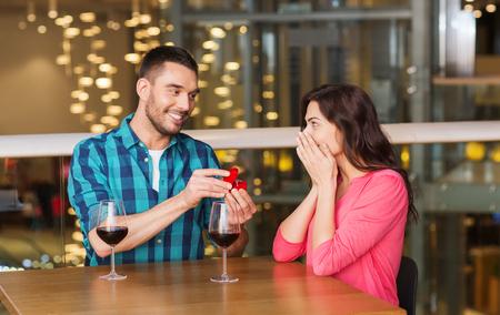 anillo de boda: la gente, la propuesta, el amor, la pareja y el concepto de vacaciones - sonriente hombre con anillo de compromiso de diamantes a su novia feliz en el restaurante Foto de archivo