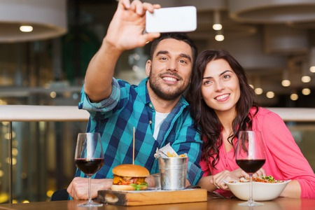 table: leisure, technology, date, people and holidays concept - happy couple having dinner and taking selfie by smartphone at restaurant