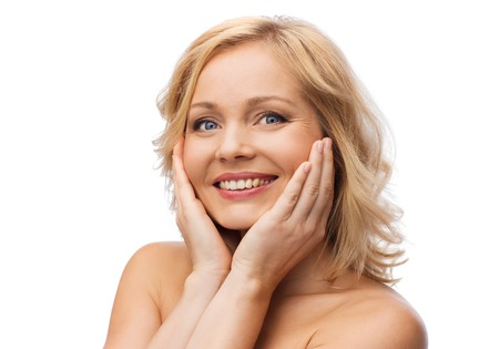 mid adult women: beauty, people and skincare concept - smiling woman with bare shoulders touching face Stock Photo