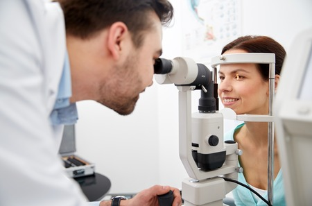 health care, medicine, people, eyesight and technology concept - optometrist with non contact tonometer checking patient intraocular pressure at eye clinic or optics store Stock Photo