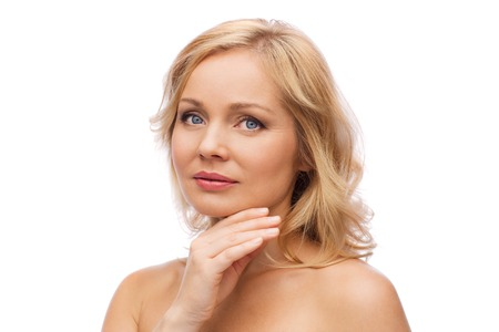 bare shoulders: beauty, people and skincare concept - smiling woman with bare shoulders touching face Stock Photo