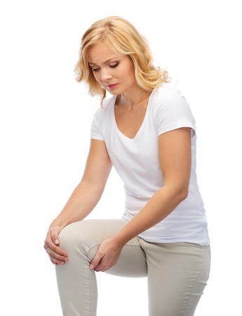 middle joint: people, healthcare and problem concept - unhappy middle aged woman suffering from pain in leg or knee at home Stock Photo