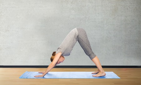 dog pose: fitness, sport, people and healthy lifestyle concept - woman making yoga in downward facing dog pose on mat over gym room background Stock Photo