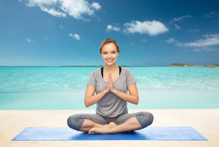 beach mat: fitness, sport, people and healthy lifestyle concept - woman making yoga meditation in lotus pose on mat over beach background