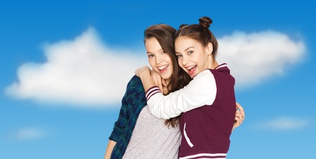 amigos abrazandose: people, friends, teens and friendship concept - happy smiling pretty teenage girls hugging over blue sky and clouds background