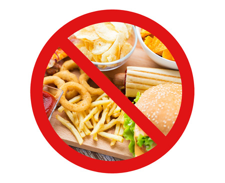 fast food, low carb diet, fattening and unhealthy eating concept - close up of deep-fried squid rings, french fries and other snacks behind no symbol or circle-backslash prohibition sign