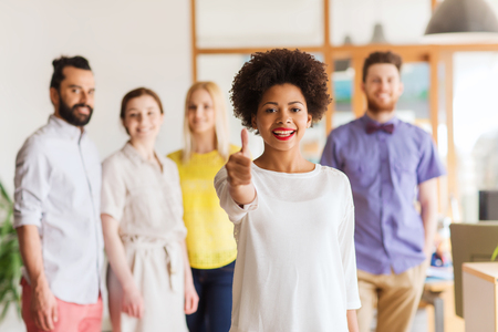 happy african woman: business, startup, people, gesture and teamwork concept - happy young african woman showing thumbs up over international creative team in office