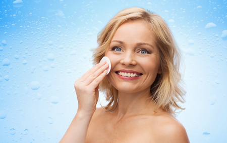 removing make up: beauty, people and skincare concept - happy middle aged woman cleaning face and removing make up with cotton pad over water drops on blue background