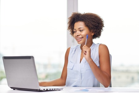 distance: education, business and technology concept - happy african american businesswoman or student with laptop computer and papers at office