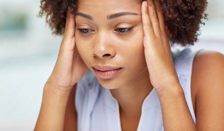 mujeres africanas: las personas, la tecnología y el concepto de ocio - feliz mujer joven afroamericano que se sienta en el sofá con el teléfono inteligente y auriculares que escucha la música y el baile en casa