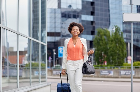 african business: travel, business trip, people and tourism concept - happy young african american woman with travel bag walking down city street Stock Photo