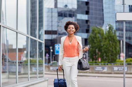 afroamericanas: viajes, viaje de negocios, la gente y el concepto de turismo - African American mujer joven feliz con bolsa de viaje caminando por calle de la ciudad Foto de archivo