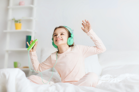 pajama party: people, children, pajama party and technology concept - happy smiling girl in headphones sitting on bed with smartphone and listening to music at home