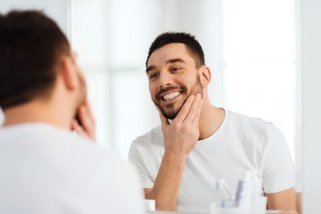 routine: beauty, hygiene and people concept - smiling young man looking to mirror at home bathroom