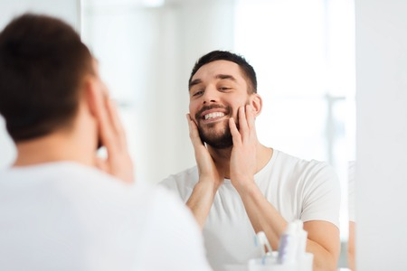 man looking: beauty, hygiene and people concept - smiling young man looking to mirror at home bathroom