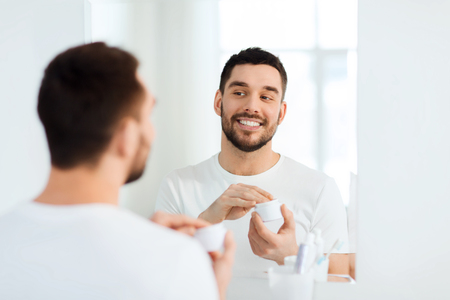 routine: beauty, skin care and people concept - smiling young man applying cream to face and looking to mirror at home bathroom