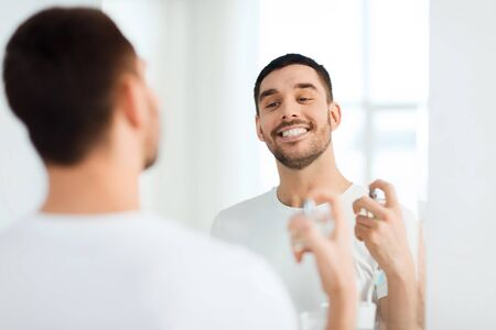 perfumery concept: perfumery, beauty and people concept - happy smiling young man with perfume looking to mirror using scent at bathroom