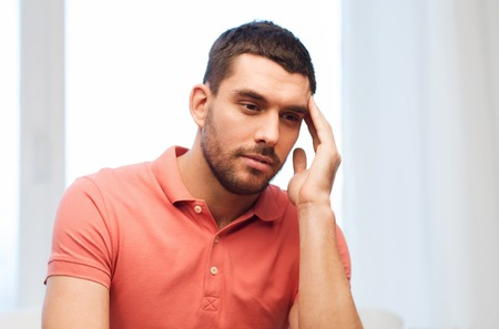 megrim: people, healthcare, stress and problem concept - unhappy man suffering from headache at home Stock Photo