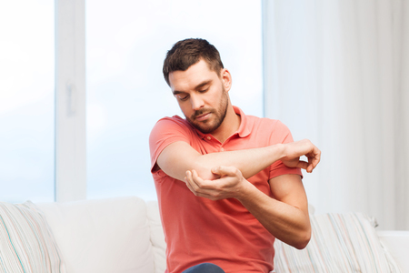 elbow pain: people, healthcare and problem concept - unhappy man suffering from pain in hand at home