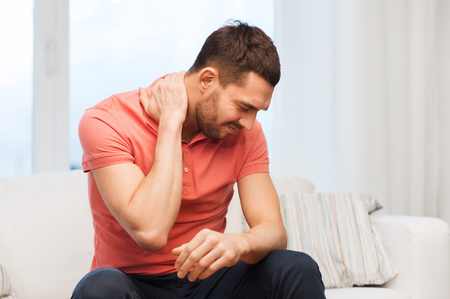 man sad: people, healthcare and problem concept - unhappy man suffering from neck pain at home