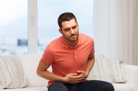 mensen, de gezondheidszorg en het probleem concept - ongelukkige man lijdt aan maagpijn thuis Stockfoto