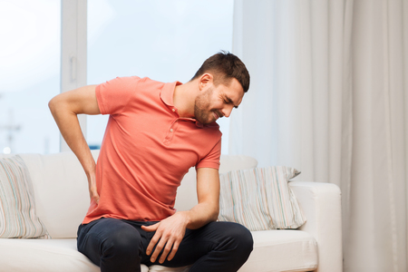 colic: people, healthcare and problem concept - unhappy man suffering from pain in back or reins at home