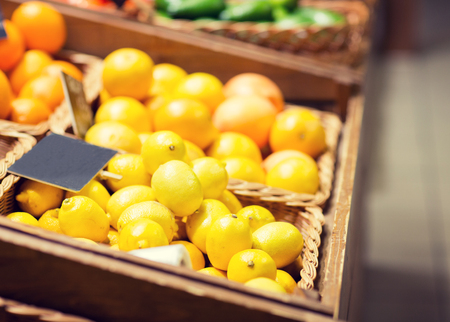 sale, shopping, vitamin c and healthy food concept - ripe lemons in basket with nameplate at grocery market Zdjęcie Seryjne