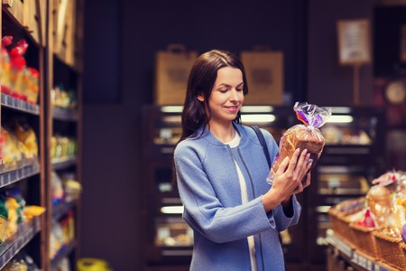 sale, shopping, consumerism and people concept - happy young woman choosing and reading label on bread in market
