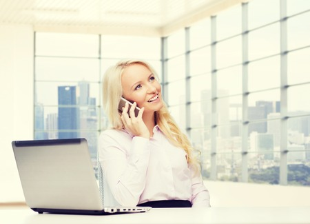 chatty: business, communication, people and technology concept - smiling businesswoman or secretary with laptop computer calling on smartphone over office room with city view window background