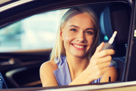 new motor car: auto business, car sale, consumerism and people concept - happy woman taking car key from dealer in auto show or salon