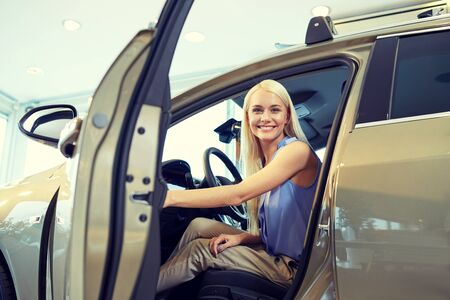 open car door: auto business, car sale, consumerism , transportation and people concept - happy woman sitting in or driving car