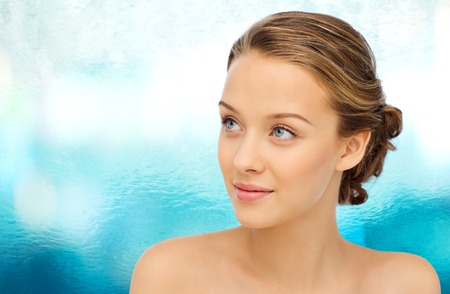 la beauté, les gens et le concept de la santé - en souriant jeune femme face et les épaules sur fond bleu de l'eau