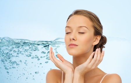 Schönheit, Menschen, feuchtigkeitsspendend, Hautpflege und Gesundheit Konzept - junge Frau das Gesicht und die Hände über Wasser spritzen Hintergrund Standard-Bild