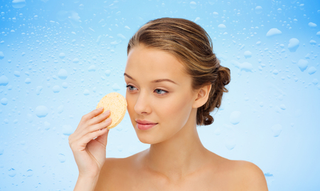 washing face: beauty, people, moisturizing, skin care and skincare concept - young woman cleaning face with exfoliating sponge over water drops on blue background