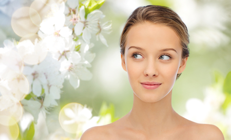 beauty, people and health concept - smiling young woman face and shoulders over summer green natural background with cherry blossom